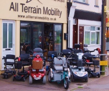 A selection of All Terrain Mobility's re-conditioned mobility scooters outside All Terrain Mobility's shop.  Featuring large four wheeled mobility scooters, large three wheeled mobility scooters, small travel mobility scooters and medium sized four wheeled mobility scooters.  All in fantastic condition and looking splendid!